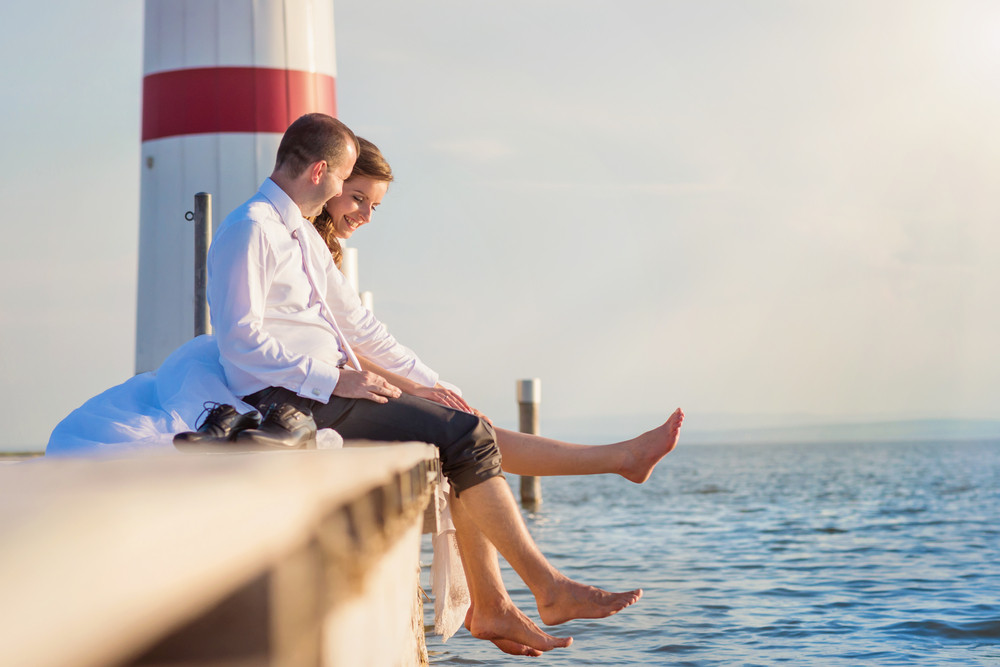 Beautiful young wedding couple sitting on the pier in front of lighthouse