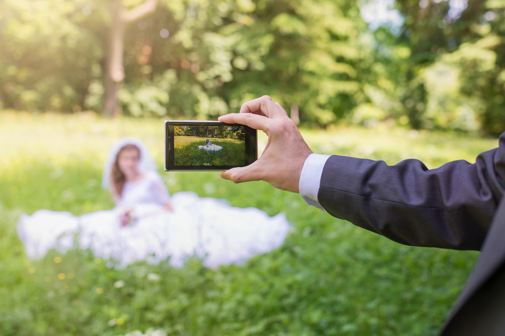 Beautiful young wedding couple taking pictures in a park
