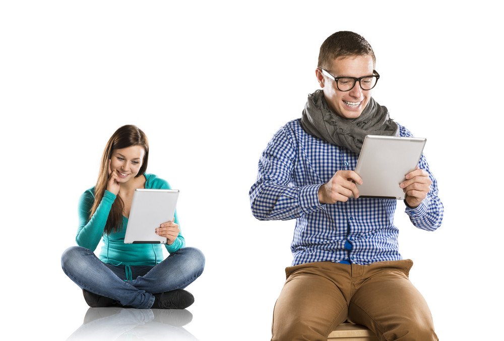 Beautiful young woman and man with tablet in studio