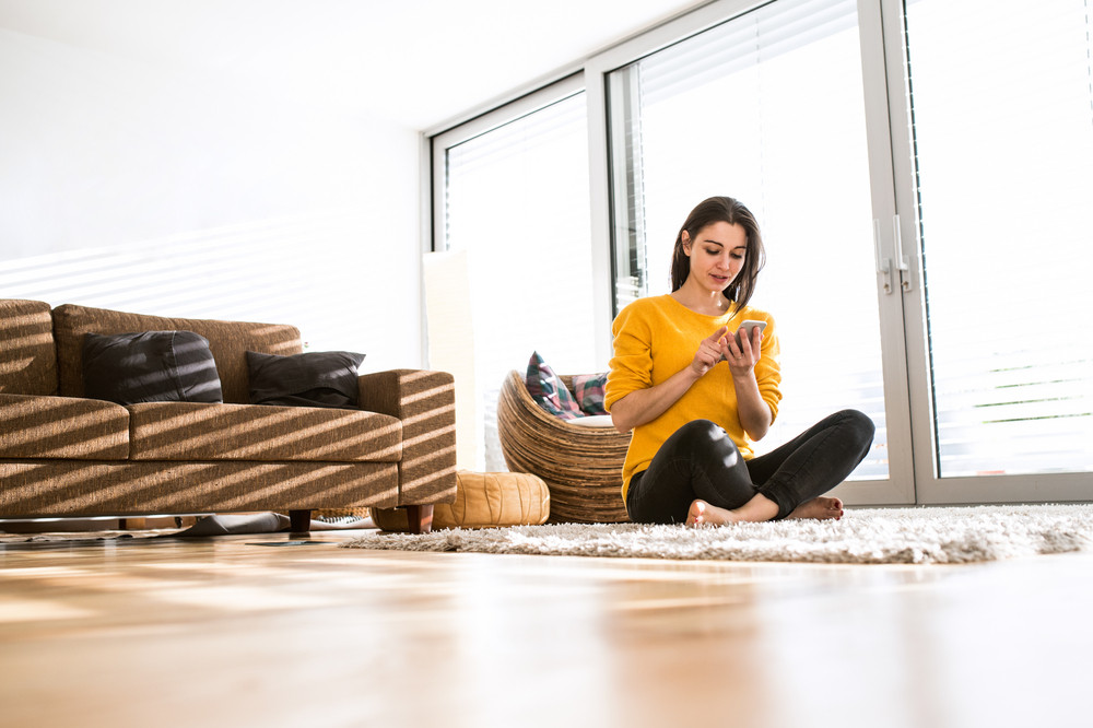 Beautiful young woman at home sitting on carpet with legs crossed, holding smart phone, texting.