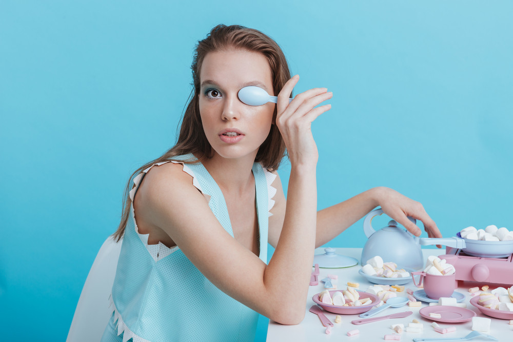 Beautiful young woman covered her eye with plastic spoon over blue background