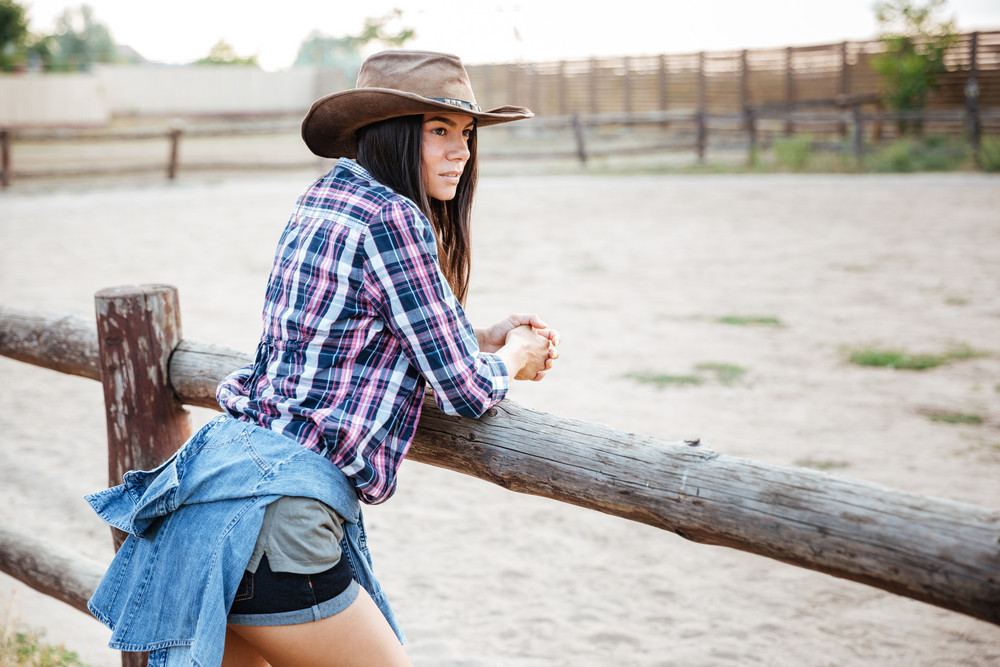 Beautiful young woman cowgirl in hat and plaid shirt standing and thinking