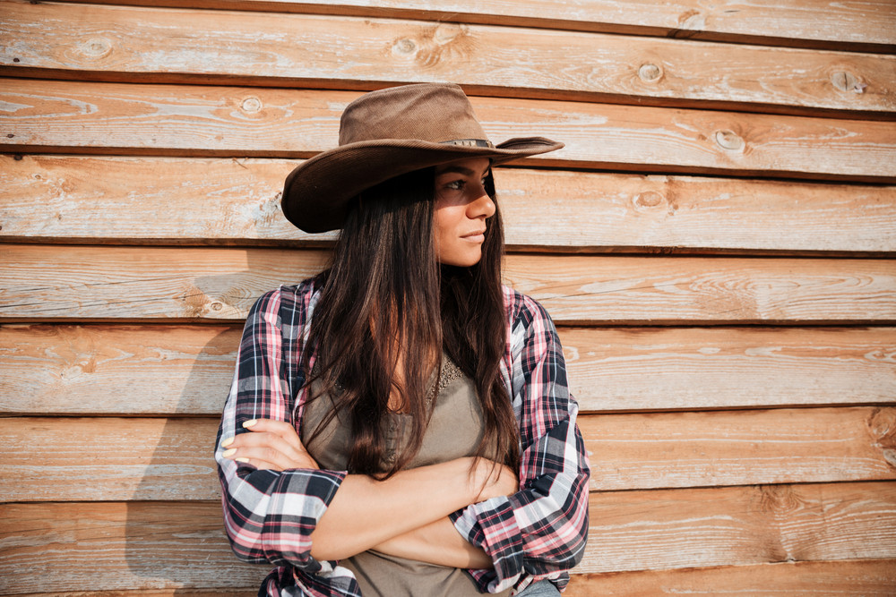 Beautiful young woman cowgirl in hat standing with arms crossed on wooden background