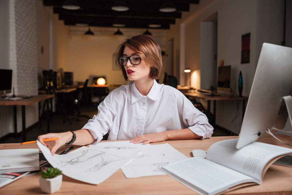 Beautiful young woman fashion designer in glasses working at the table in office