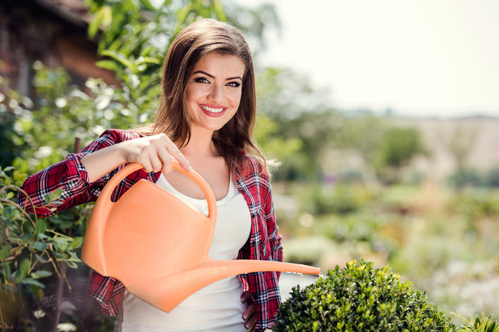 Beautiful young woman gardening outside in summer nature