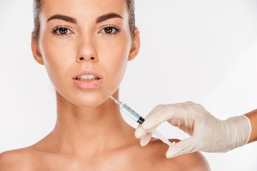 Beautiful young woman gets beauty injection in lips with syringe isolated on white background