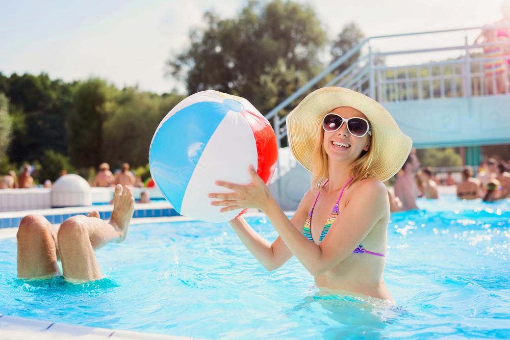 Beautiful young woman having fun outside in the swimming pool