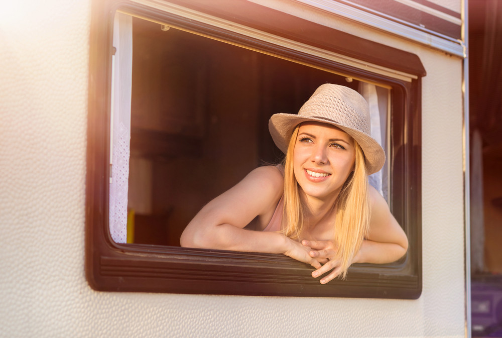 Beautiful young woman in a camper van on a summer day