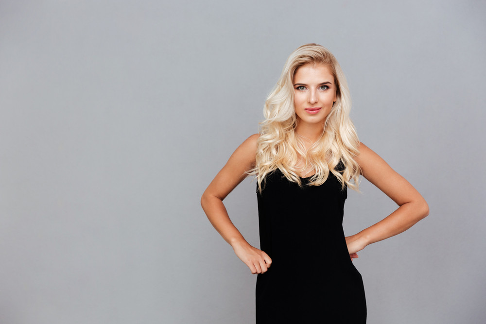 Beautiful young woman in black dress posing isolated on a gray background