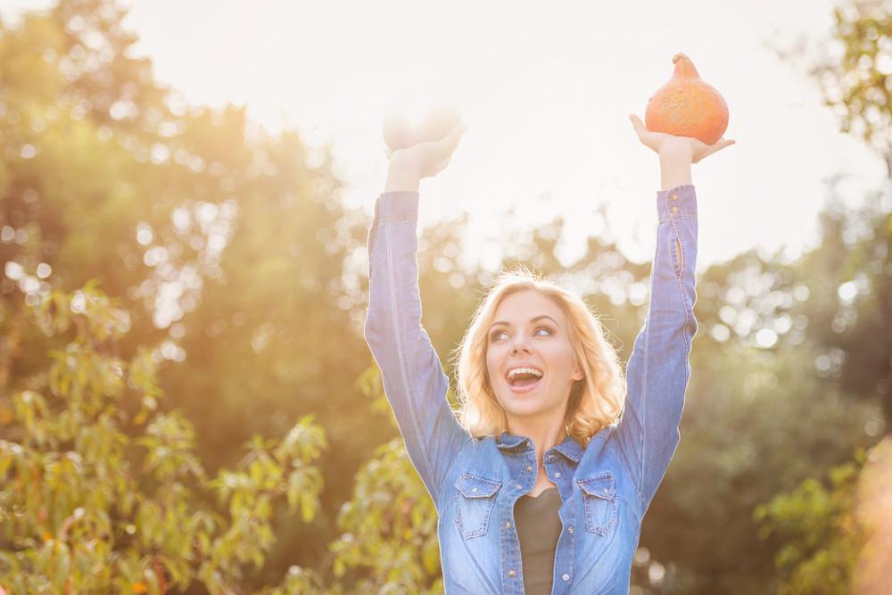 Beautiful young woman in denim shirt harvesting pumpkins