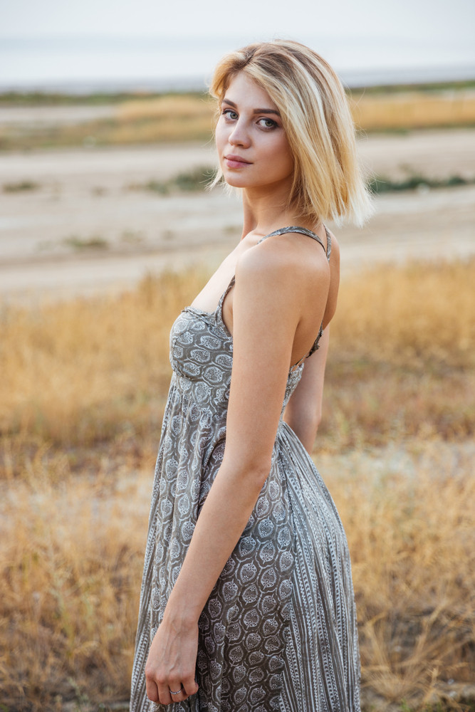 Beautiful young woman in dress standing outdoors