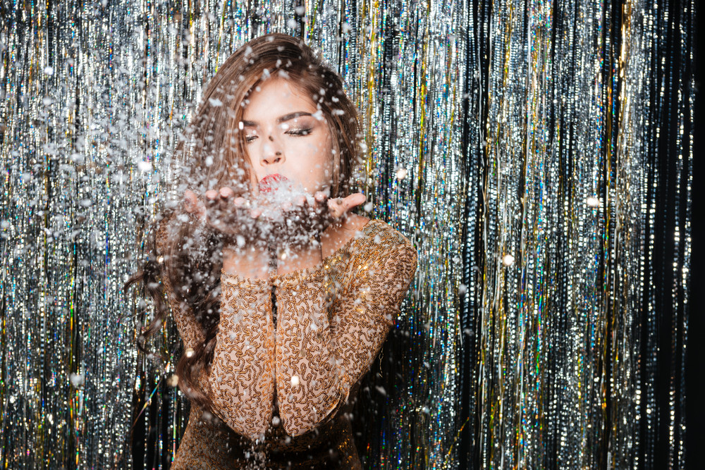 Beautiful young woman in evening dress standing and blowing on snowflakes in her hands over shining background