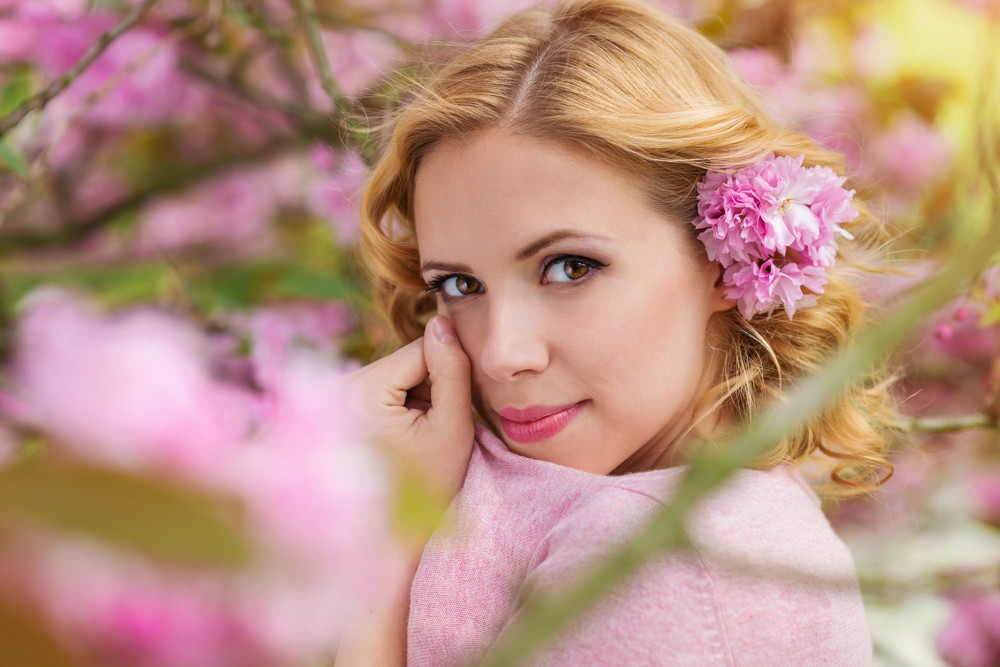 Beautiful young woman in front of a tree in blossom