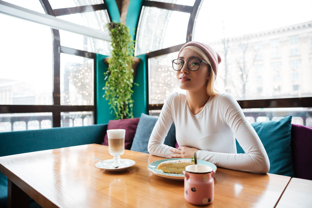 Beautiful young woman in hat and glasses drinking coffee and eating cake in cafe