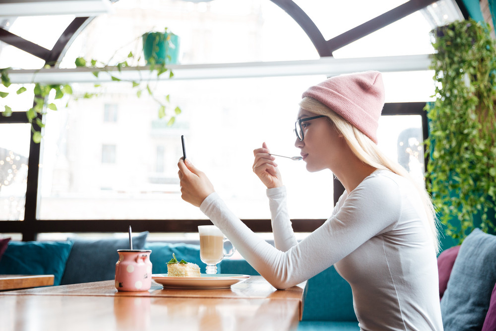 Beautiful young woman in hat and glasses eating dessert and using cell phone in cafe