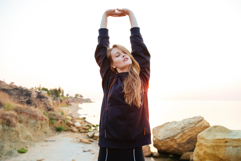 Beautiful young woman in hoodie stretching hands while standing on the beach