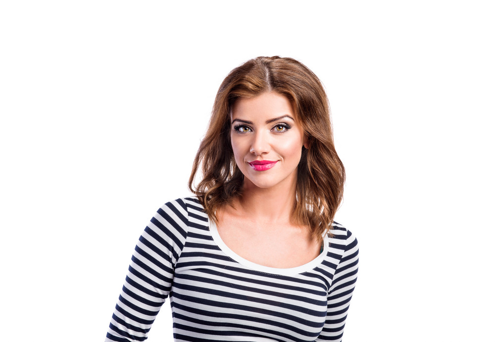 Beautiful young woman in jeans and striped long sleeved t-shirt. Studio shot on white background, isolated.