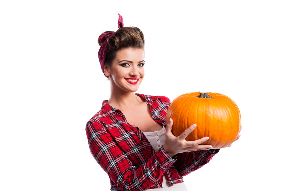 Beautiful young woman in red checked shirt with pin-up make-up and hairstyle holding orange pumpkin. Studio shot on white background. Autumn harvest