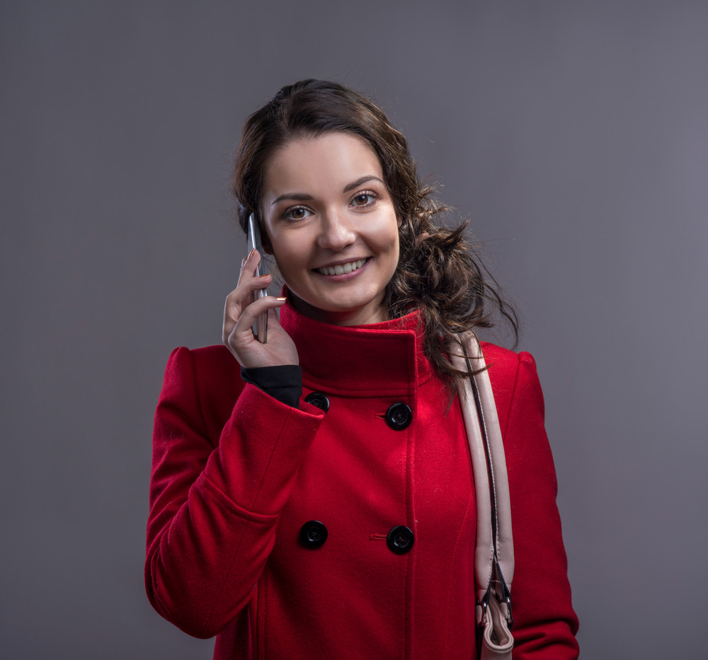 Beautiful young woman in red coat with smart phone. Studio shot on ...