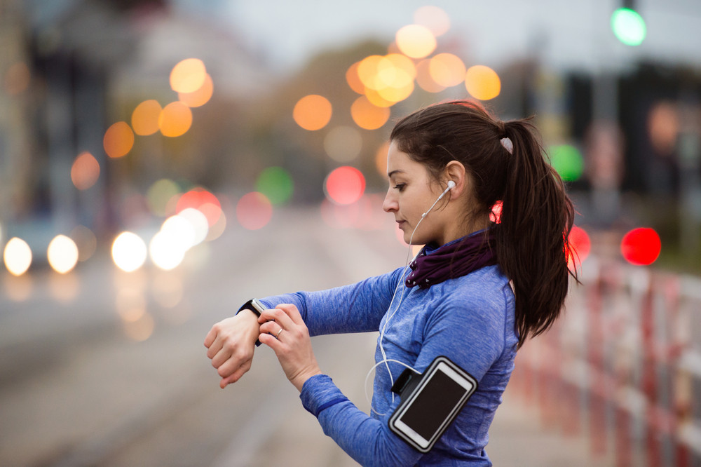Beautiful young woman in the city with smart phone, smartwatch and earphones, listening music. Using a fitness app for tracking weight loss progress, running goal or summary of her run. Rear view.