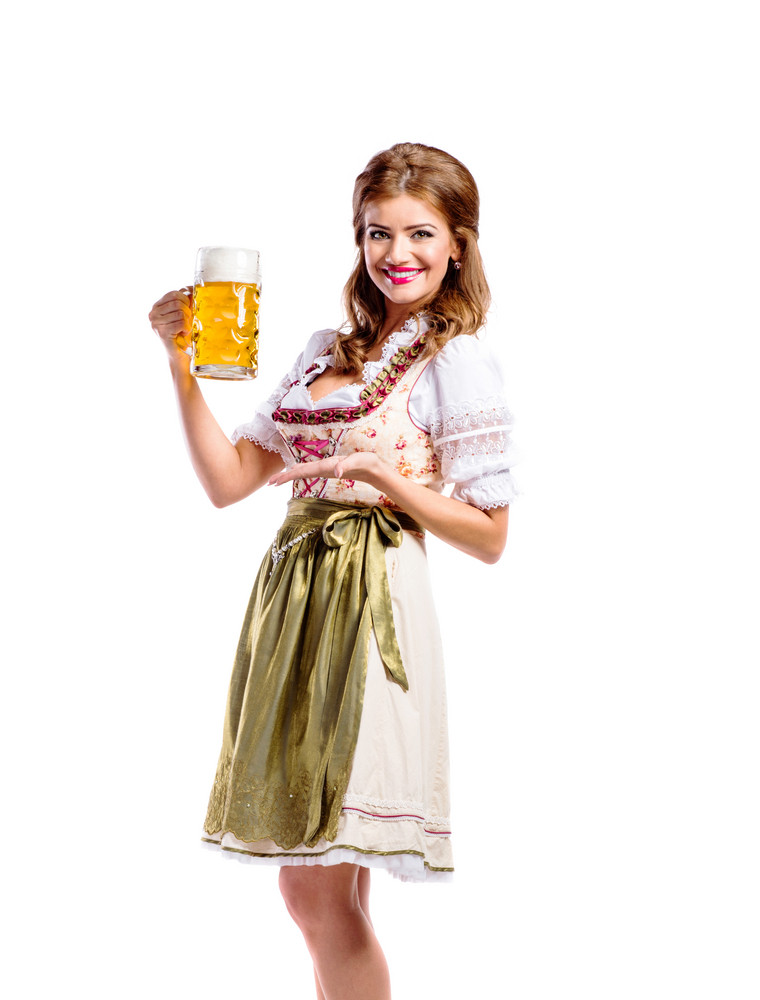 Beautiful young woman in traditional bavarian dress holding a mug of beer. Oktoberfest. Studio shot on white background, isolated.