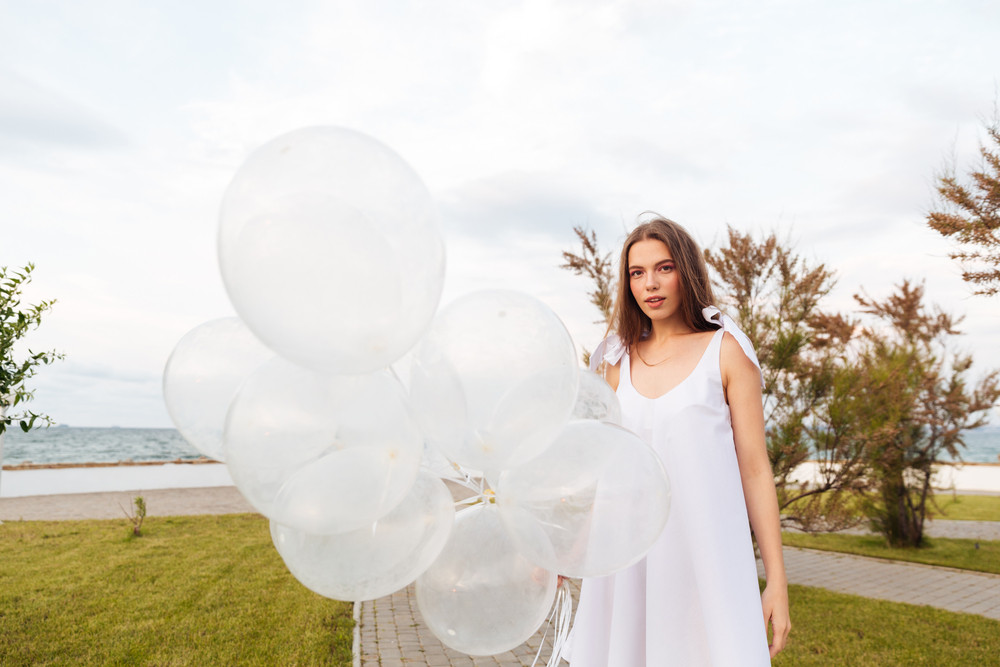 Beautiful young woman in white dress standing outdoors and holding balloons