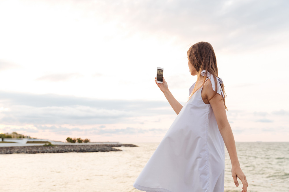 Beautiful young woman in white dress taking photos with mobile phone on the seaside
