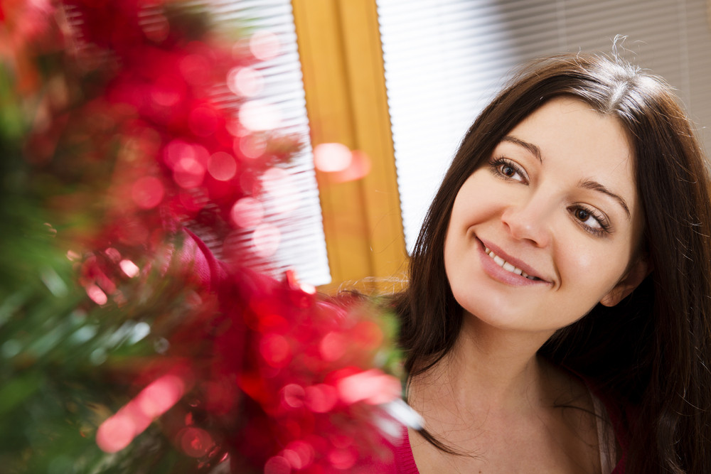 Beautiful young woman is decorating christmas tree.
