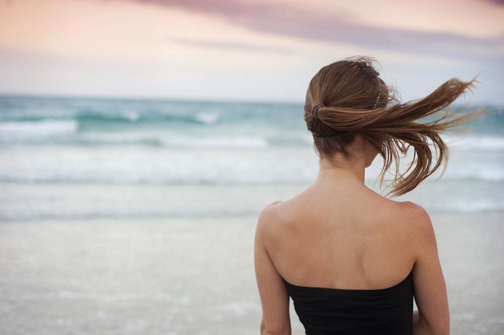 Beautiful young woman is enjoying free time at the beautiful sandy beach