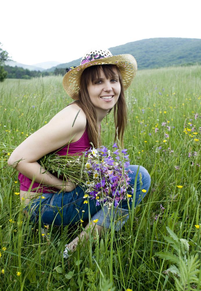 Beautiful young woman is enjoying nature in green meadow