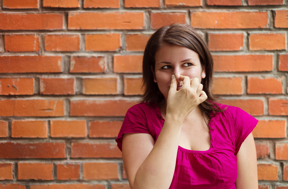 Beautiful young woman making funny faces on a brick wall background