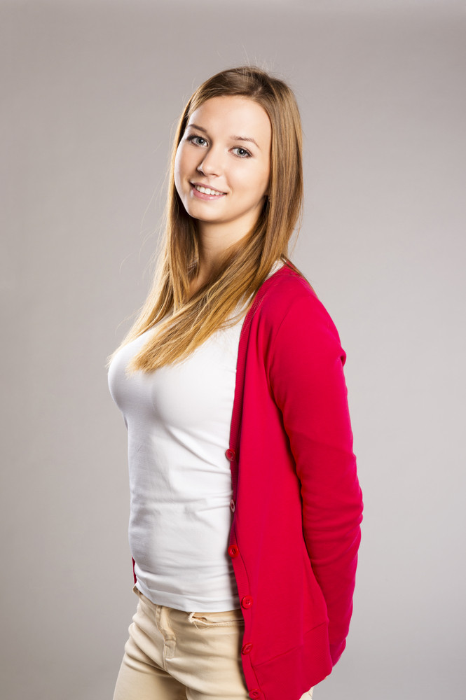 Beautiful young woman posing in studio over a gray background