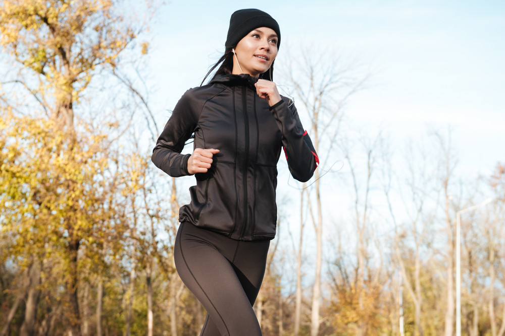 Beautiful young woman runner in warm clothes and earphones running in autumn park