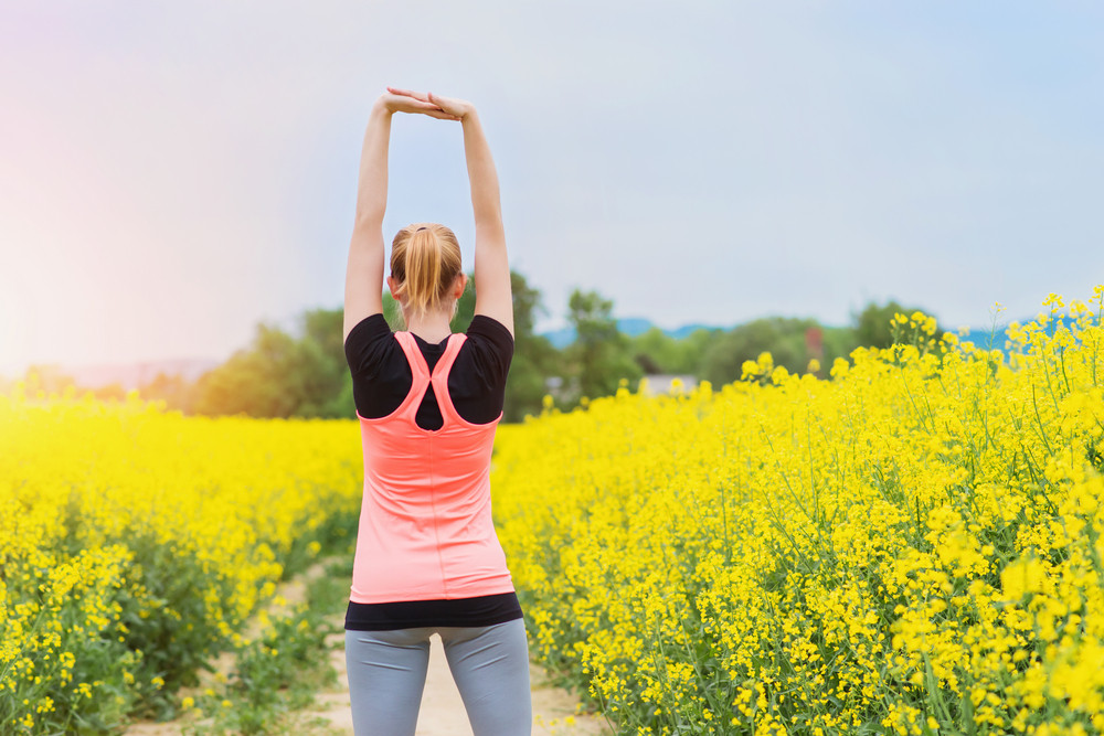 Beautiful young woman running outside in spring canola field