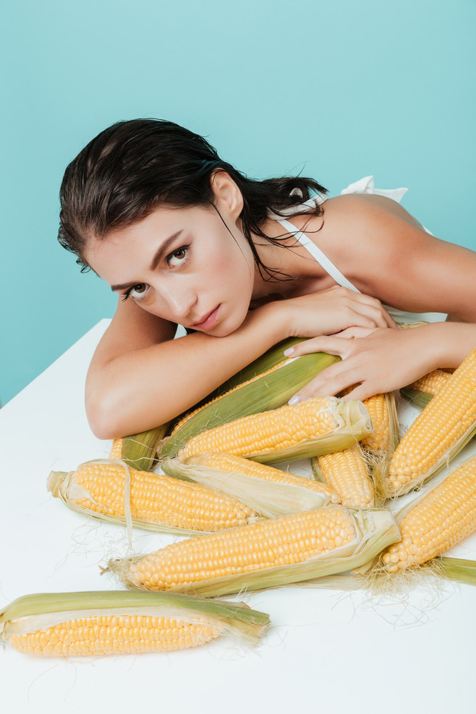 Beautiful young woman sitting and leaning on the table with corn cobs over blue background