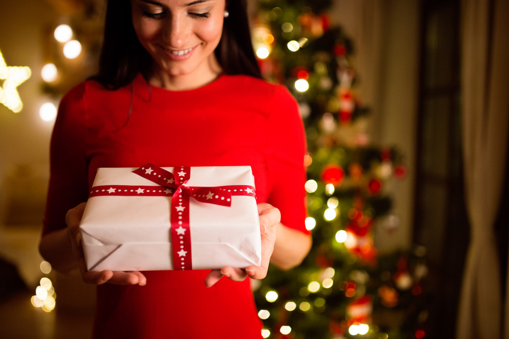Beautiful young woman sitting in front of illuminated Christmas tree inside in her house giving or receiving present.