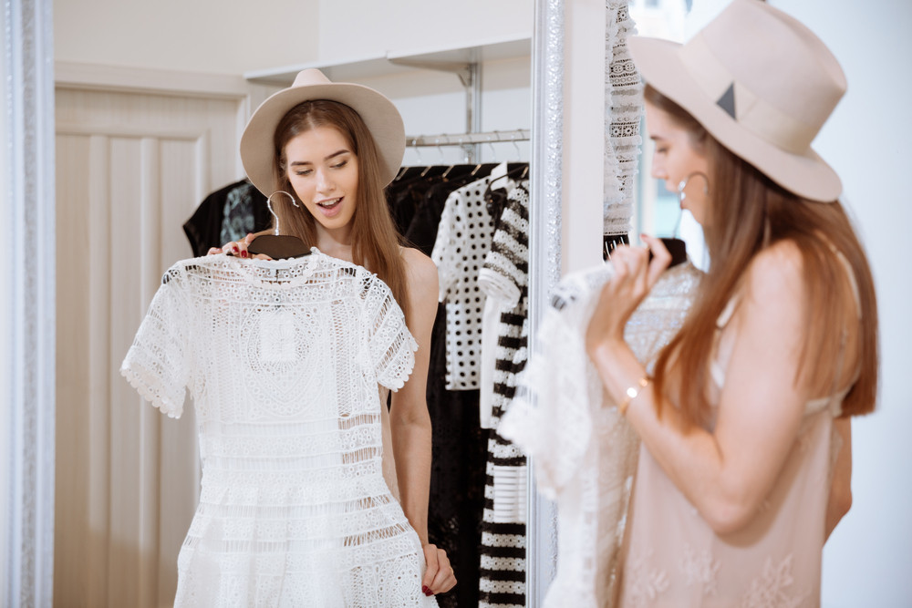 Beautiful young woman standing and trying on dress in front of mirror