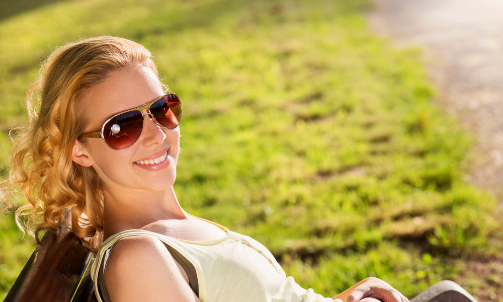 Beautiful young woman wearing sunglasses outside in sunny summer nature
