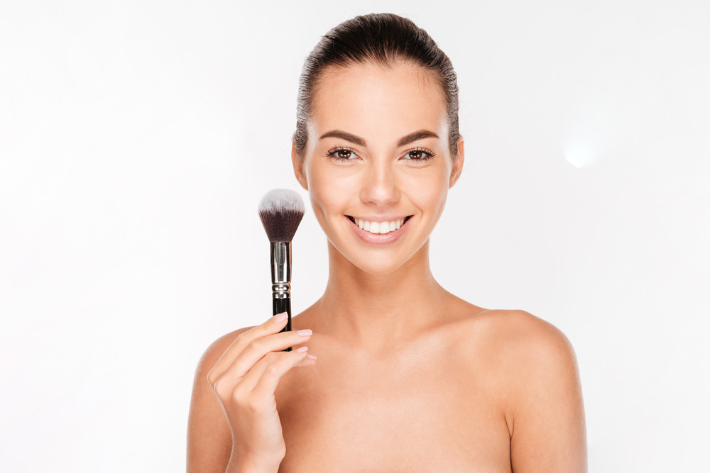 Beautiful young woman with a make-up brush isolated on white background