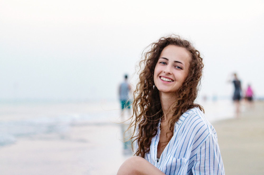 Beautiful young woman with curly hair sitting on beach wearing striped blue and white shirt, smiling. Enjoying time at seaside.