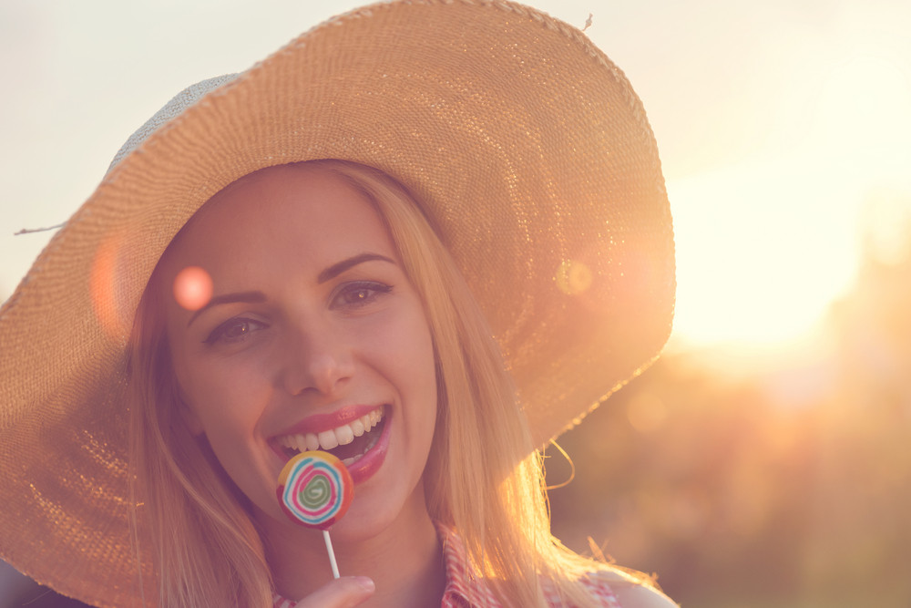 Beautiful young woman with lollipop outside on a sunny day