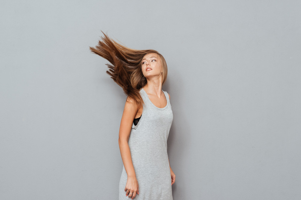 Beautiful young woman with long hair and eyes closed posing isolated on a gray background