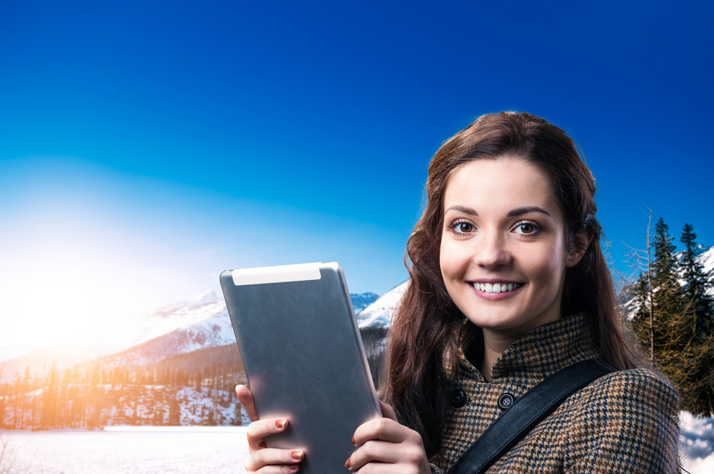 Beautiful young woman with tablet enjoying a walk in mountains