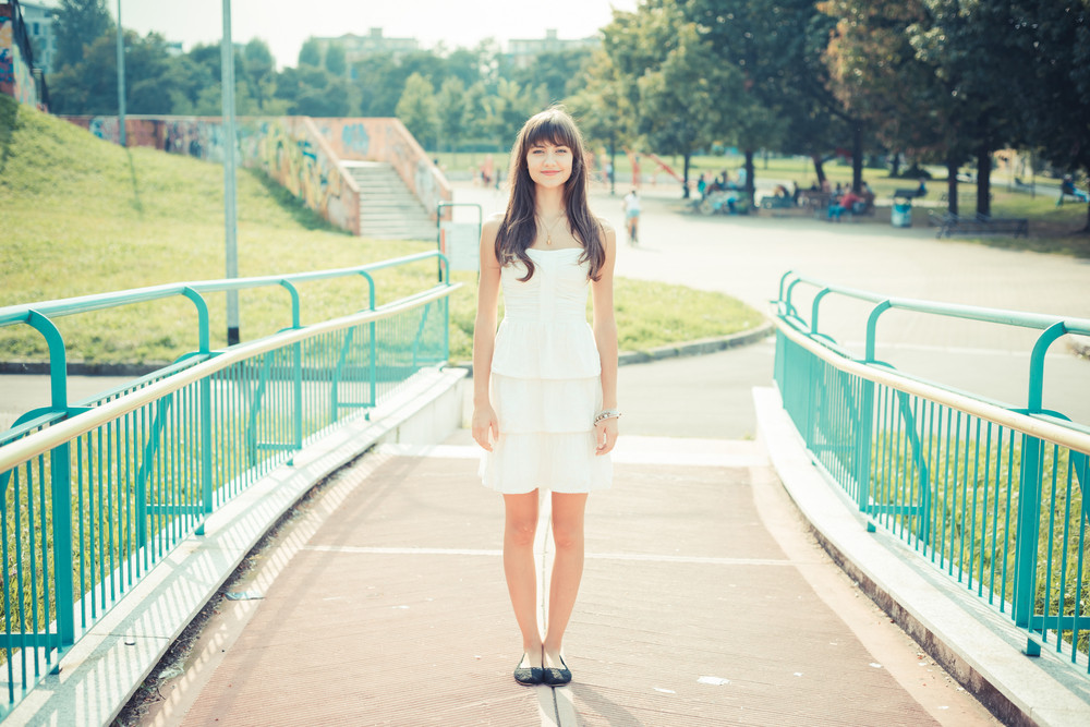 beautiful young woman with white dress in the city