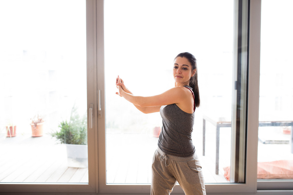 Beautiful young woman working out at home in living room, doing yoga or pilates exercise, stretching arms.