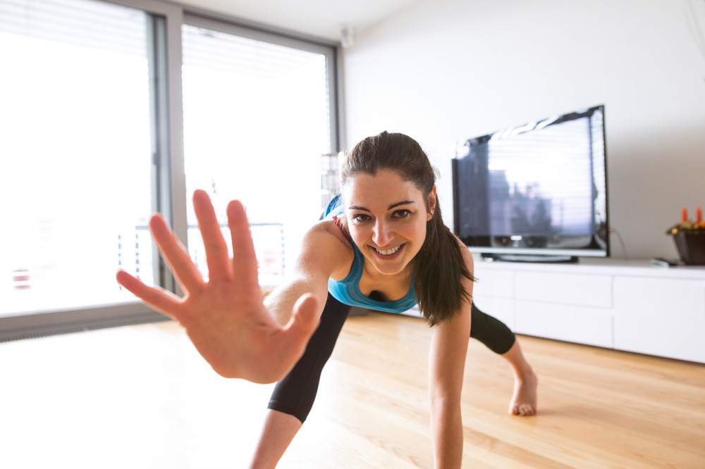Beautiful young woman working out at home in living room, doing yoga or pilates exercise, stretching legs and arms.