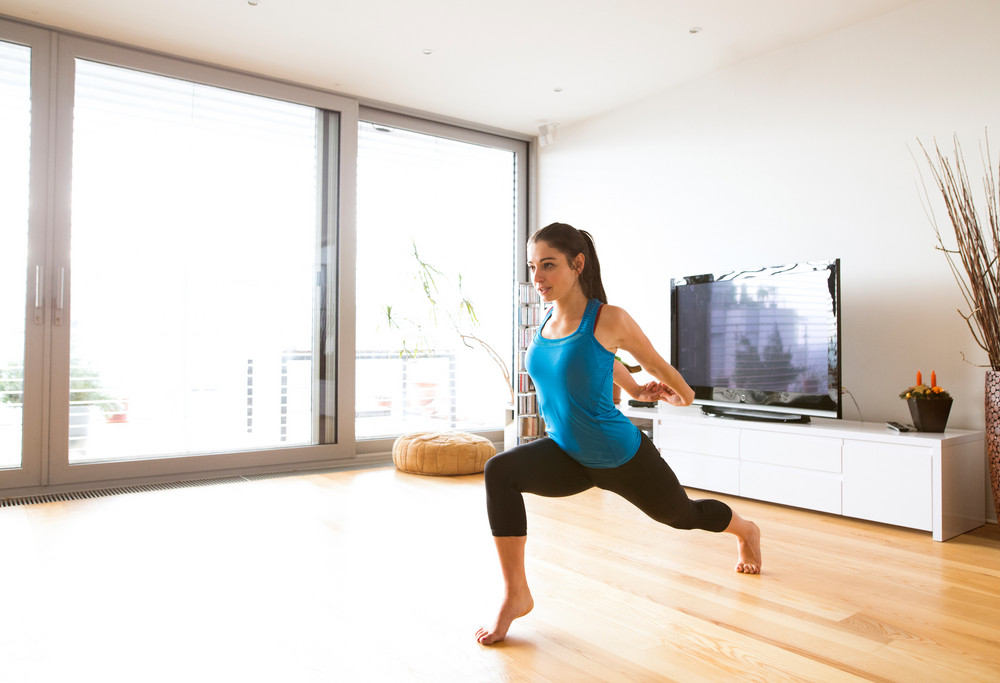 Great Beautiful Young Woman Working Out At Home In Living Room, Doing Yoga Or  Pilates Exercise, Stretching Legs And Arms.