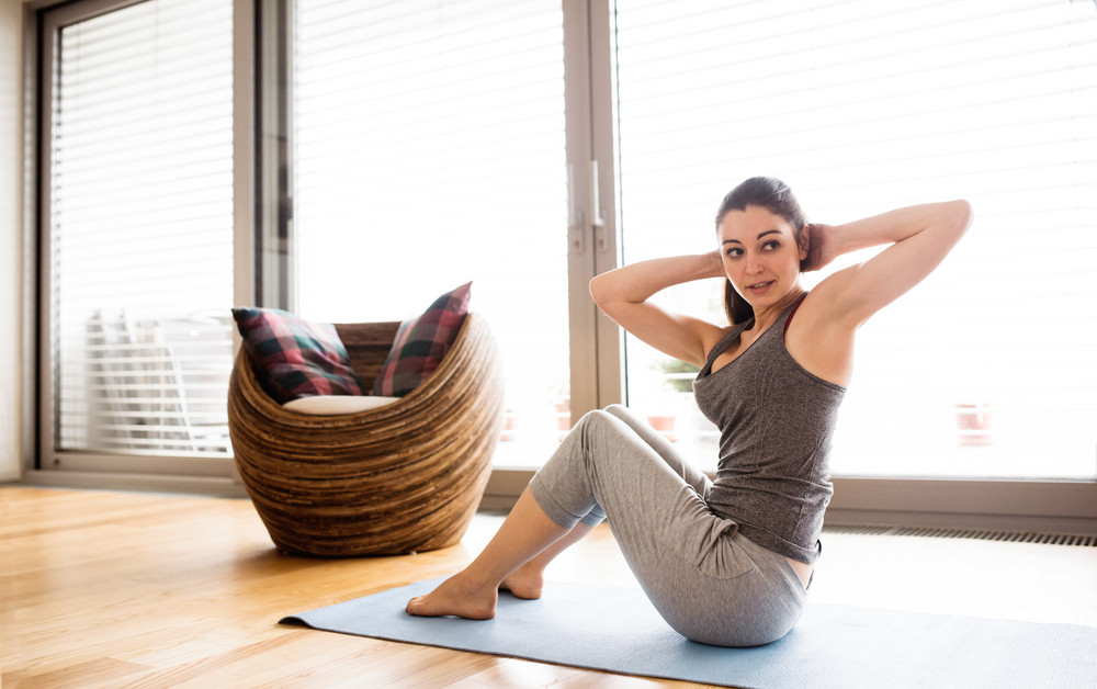 Beautiful Young Woman Working Out At Home In Living Room