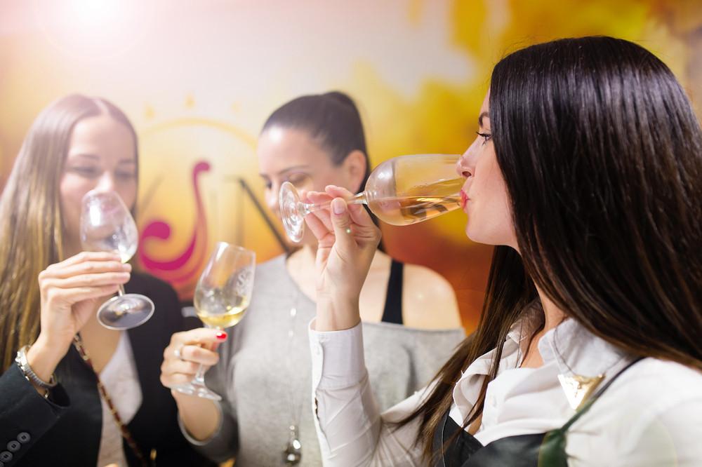 Beautiful young women having fun outside in wine bar