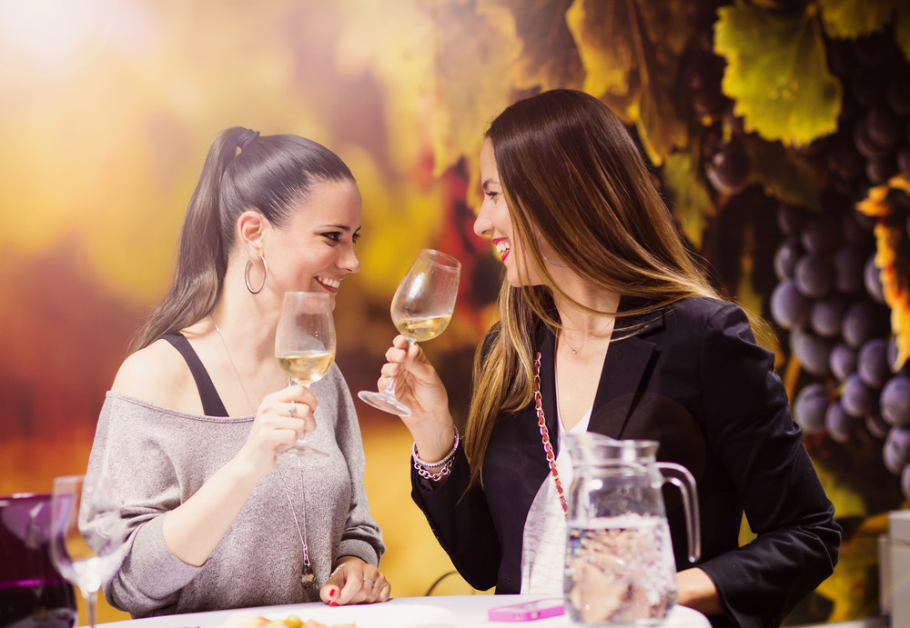 Beautiful young women having fun outside in wine bar